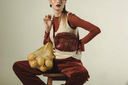 Photo pour Vue recadrée d'une fille à la mode assise sur un tabouret avec des citrons dans un sac à ficelle isolé sur beige - image libre de droit