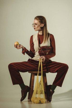 Photo pour Belle fille assise sur tabouret avec des citrons dans un sac à ficelle sur beige - image libre de droit