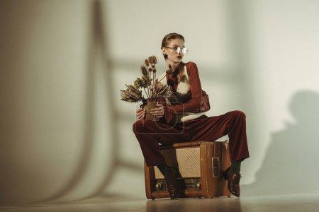 Photo pour Fille à la mode maintenant bouquet de fleurs séchées et assis sur vintage tv sur beige - image libre de droit
