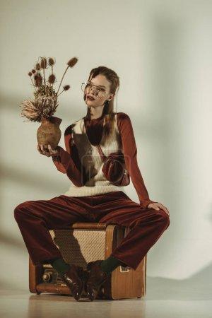 Photo pour Jolie femme tenant le bouquet de fleurs séchées et assis sur vintage tv sur beige - image libre de droit
