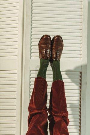Photo pour Recadrée vue des jambes féminines dans les chaussures en cuir vintage près de paravent - image libre de droit