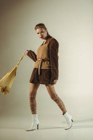 Photo pour Jolie fille à la mode, la marche avec citrons dans sac chaîne sur beige - image libre de droit