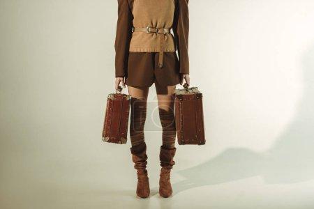 Photo pour Vue recadrée de jeune femme tenant des sacs de voyage vintage sur beige - image libre de droit