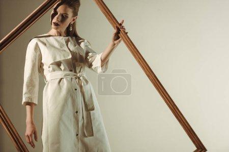 Photo pour Fille élégante en blanc tenue trendy posant avec grand cadre en bois, isolé sur beige - image libre de droit