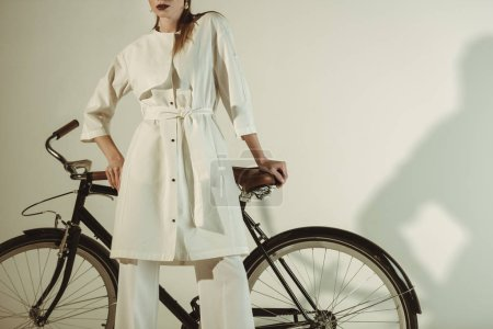 Photo pour Recadrée vue de jeune fille à la mode en tenue blanche posant sur vélo - image libre de droit