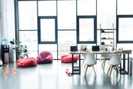 modern design of spacious loft office with bean bag chairs and table with laptops
