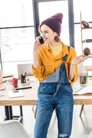 Photo pour Une gestuelle concepteur femelle avec la main et utilisant le smartphone au bureau loft - image libre de droit