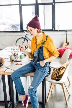 Foto de Mujer diseñador sentado en mesa y con smartphone en oficina loft - Imagen libre de derechos