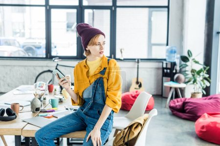 Photo for Female designer sitting on table and using smartphone in loft office with copy space - Royalty Free Image