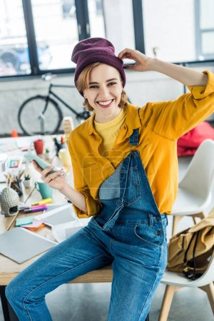 beautiful smiling female designer sitting on table and using smartphone in loft office