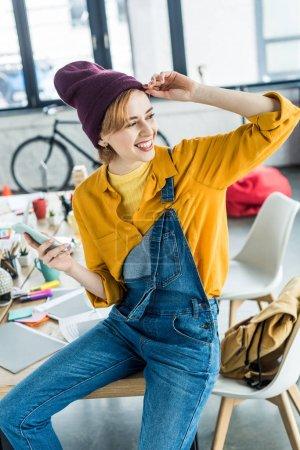 Foto de Hermosa mujer sonriente diseñador sentado en la mesa y el uso de teléfono inteligente en la oficina loft - Imagen libre de derechos