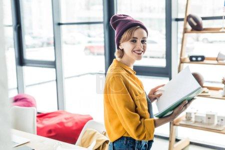 Photo pour Beau sourire holding concepteur femelle pour ordinateur portable au bureau loft - image libre de droit