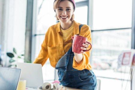 souriant jeune femme il spécialiste au bureau d'ordinateur tenant tasse de café et regardant la caméra dans le bureau loft