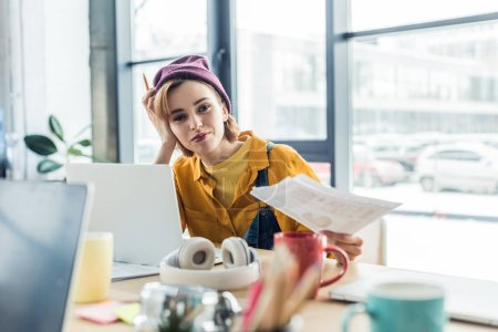 young female it specialist holding document and pen while sitting at computer desk in loft office