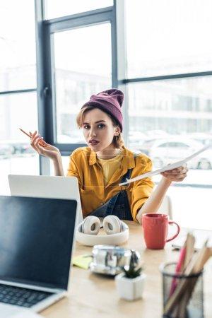 Foto de Confunde la hembra joven especialista con documento y pluma mientras está sentado en el escritorio de la computadora en la oficina de loft - Imagen libre de derechos
