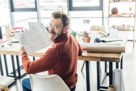 Foto de Arquitecto hombre guapo sentado en el escritorio y trabajar en planos en la oficina de loft - Imagen libre de derechos