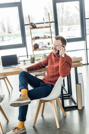 male architect sitting at computer desk and talking on smartphone in loft office