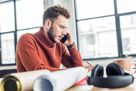 Foto de Enfoque selectivo del arquitecto hombre sentado en el escritorio, hablando por teléfono inteligente y trabajando en planos en la oficina de loft - Imagen libre de derechos