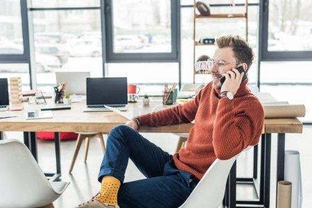 Photo pour Bel homme d'affaires décontractée assis au bureau de l'ordinateur et parler sur smartphone au bureau loft - image libre de droit