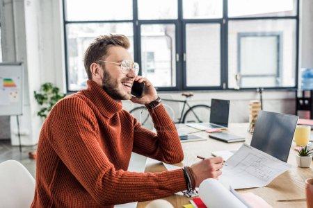 Foto de Sonriente a hombre arquitecto sentado en el escritorio, hablando por teléfono inteligente y trabajando en planos en la oficina de loft - Imagen libre de derechos