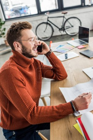 Photo for Smiling male architect sitting at desk, talking on smartphone and working on blueprint in loft office - Royalty Free Image