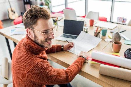 Photo pour Bel architecte masculin souriant assis au bureau et travaillant sur des plans dans le bureau loft - image libre de droit