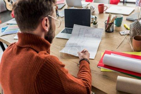 Foto de Vista posterior de arquitecto hombre sentado en el escritorio de la computadora y trabajando en planos en la oficina de loft - Imagen libre de derechos