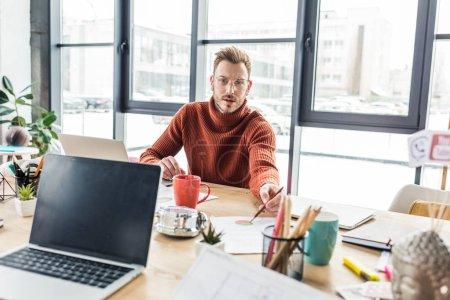 Foto de Apuesto hombre de negocios casual sentado en el escritorio de la computadora, mirando a cámara y trabajar en documentos en la oficina de loft - Imagen libre de derechos