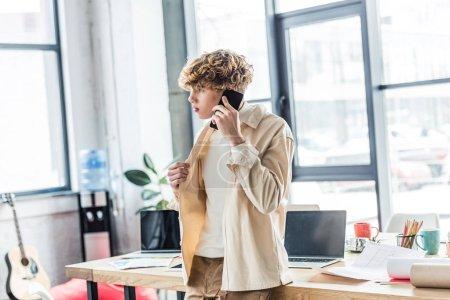 Foto de Apuesto arquitecto hablando en teléfono inteligente junto a la mesa con planos en oficina loft - Imagen libre de derechos