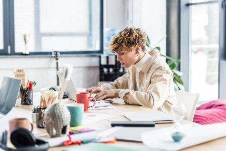 Foto de Apuesto arquitecto trabajando en el escritorio de la computadora con planos en oficina loft - Imagen libre de derechos