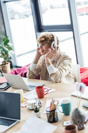 Photo for Handsome smiling it specialist in headphones sitting at desk and using laptop in loft office - Royalty Free Image