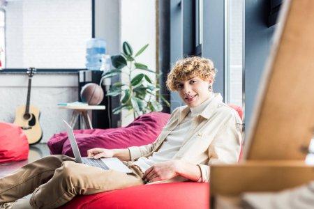 Photo pour Bel homme d'affaires décontractée assis dans la chaise de sac d'haricot et regardant la caméra tout en utilisant le portable de bureau loft - image libre de droit