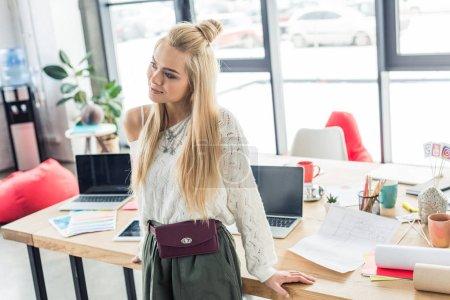 Foto de Hermosa mujer arquitecto junto a la mesa con planos y ordenadores portátiles en la oficina de loft - Imagen libre de derechos