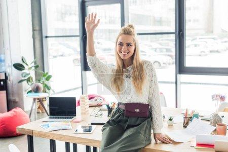 Foto de Hermosa arquitecto mujer sonriente que agita cerca de mesa y ordenador portátil en la oficina de loft planos - Imagen libre de derechos