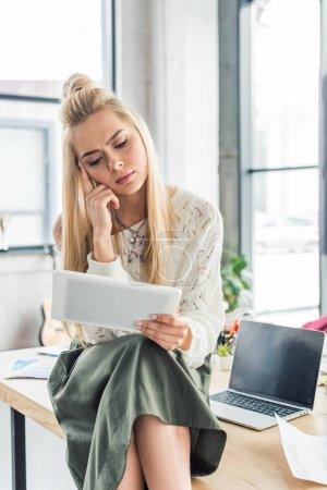 Photo pour Belle femme casual pensive assis au bureau de l'ordinateur et à l'aide de tablette numérique au bureau loft - image libre de droit