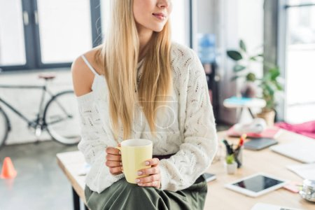 Photo for Cropped view of casual businesswoman sitting and having coffee break in loft office - Royalty Free Image