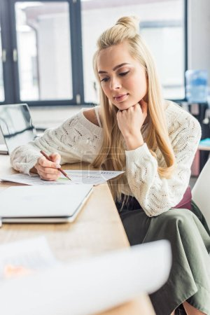 Photo for Beautiful female architect working on blueprint in loft office - Royalty Free Image