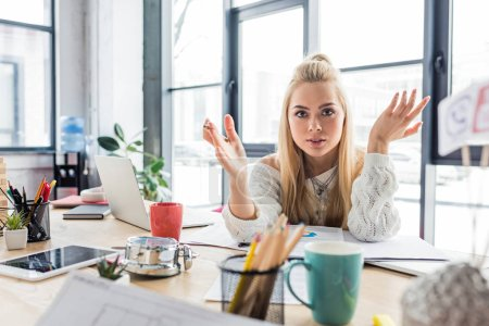 confused female architect gesturing with hands while sitting at computer desk in loft office