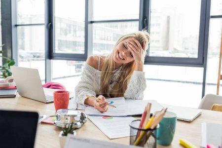 Foto de Sonriendo a empresaria femenina casual sentado en la mesa y trabajar en gráficos en la oficina de loft - Imagen libre de derechos