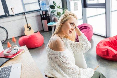belle femme d'affaires occasionnelle fatiguée assise au bureau de l'ordinateur dans le bureau loft et regardant loin