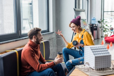 smiling female and male architects with coffee to go working on house model in loft office