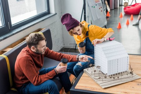 concentrated female and male architects with coffee to go working on house model in loft office