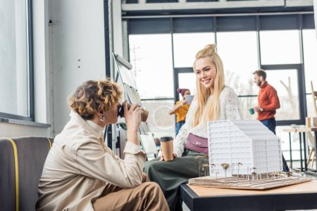female and male architects with coffee to go looking at each other while working on house model in loft office