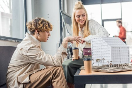 female and male architects with coffee to go working on house model in loft office