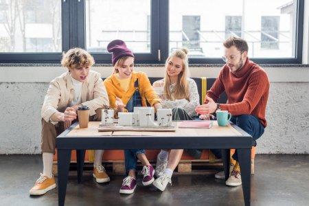Foto de Sonriente grupo de arquitectos y sentado en la mesa y trabajar en la casa modelo en la oficina de loft - Imagen libre de derechos