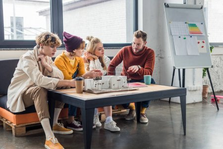 Foto de Grupo de arquitectos y sentado en la mesa y trabajar en la casa modelo en la oficina de loft - Imagen libre de derechos