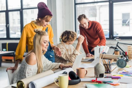 Photo for Group of female and male designers working on startup project with laptops and blueprints in loft office - Royalty Free Image
