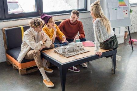 Photo pour Groupe d'architectes féminins et masculins assis à table et travailler sur le modèle de maison dans le bureau loft - image libre de droit