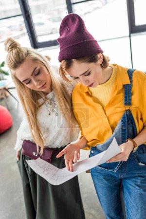 Foto de Hermosa arquitectos femenino enfocados trabajando en planos en la oficina de loft - Imagen libre de derechos