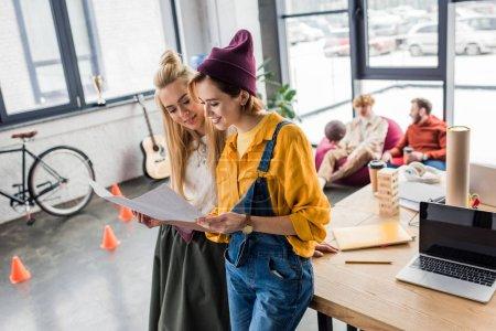 Photo pour Beau sourire femmes architectes travaillant sur plan directeur au bureau loft - image libre de droit